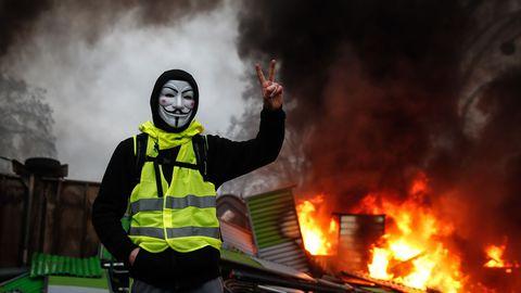 un-manifestant-portant-un-gilet-jaune-et-un-masque-pres-d-une-barricade-en-feu-a-paris-le-1er-decembre-2018_6134064 Ouverture de Conscience et théories du complot.